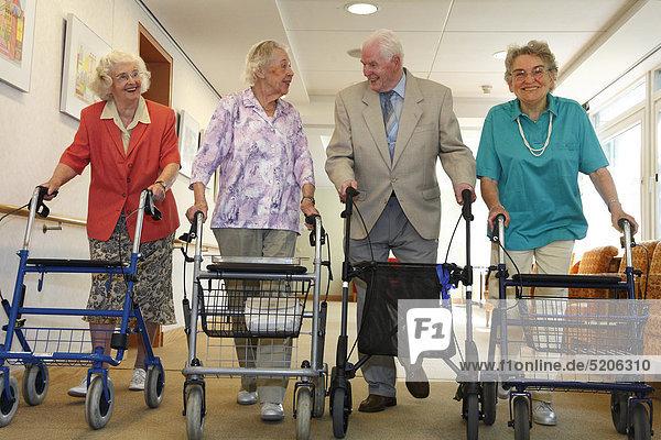 Seniorinnen und Senior gehen mit Gehwagen über Gang