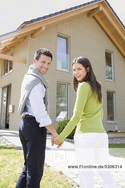 Paar vor Einfamilienhaus