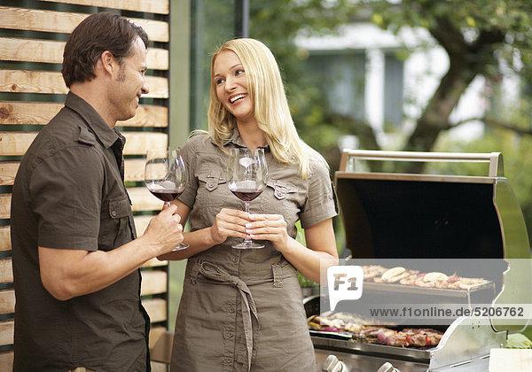 Paar beim Grillen auf Terrasse  trinken Rotwein