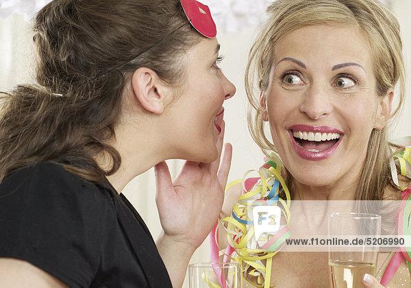 Zwei Frauen flüstern sich bei Feier etwas ins Ohr
