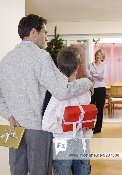 Vater und Sohn überraschen Mutter mit Weihnachtspäckchen
