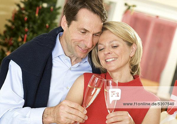 Paar an Weihnachten  stoßen mit Sekt an