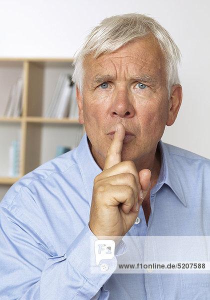 Senior mit Gestik Finger vor dem Mund