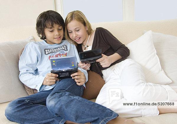 Junge und Mädchen mit kleinen Spielecomputern auf Sofa