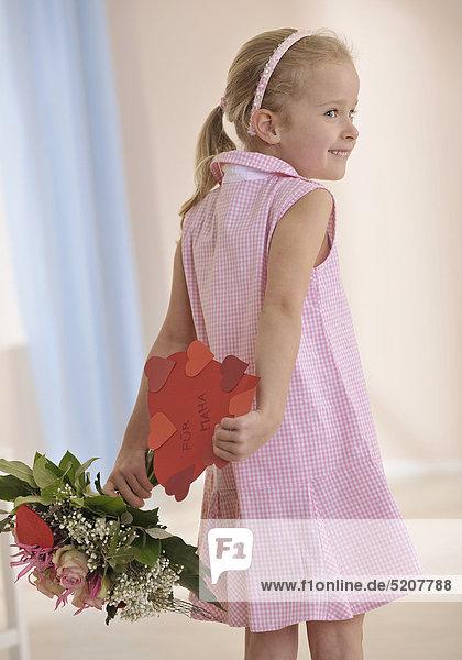 Muttertag  kleines Mädchen versteckt Herz und Blumenstrauß hinter Rücken