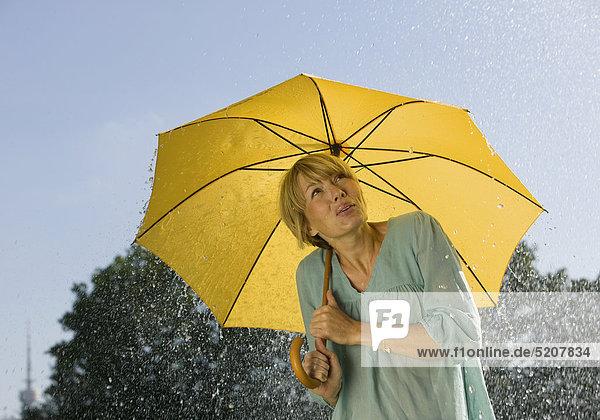 Frau steht unter Regenschirm im Regen Frau steht unter Regenschirm im Regen