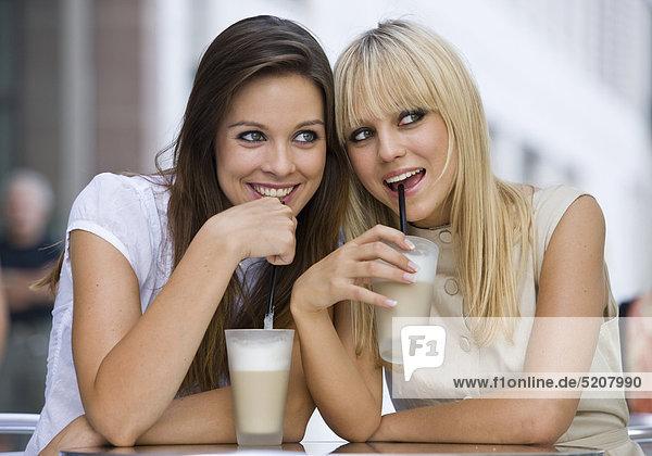 Zwei Frauen sitzen in Straßencafe  beobachten