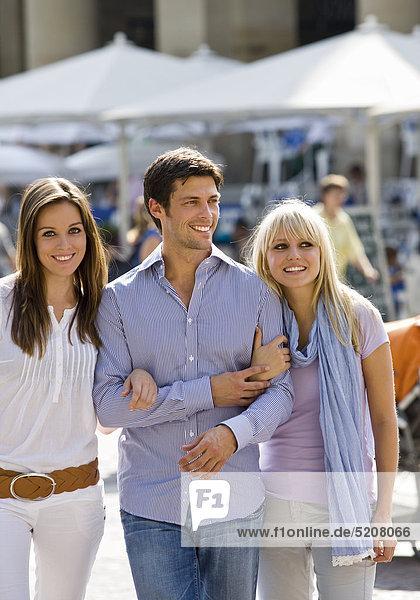 Mann mit zwei Frauen am Arm in der Stadt Mann mit zwei Frauen am Arm in der Stadt
