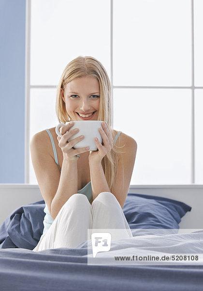 Frau trinkt im Bett große Tasse Tee