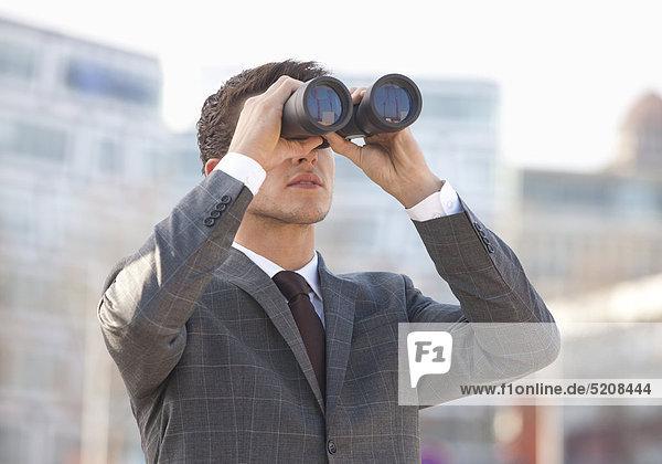 Mann schaut durch Fernglas