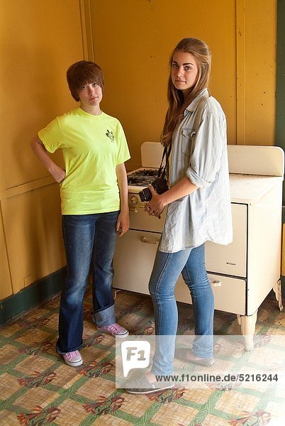 two teen girls stand in teh kitchen of an abandoned house