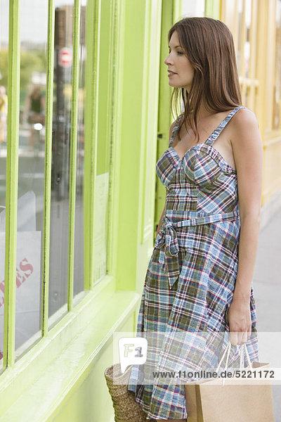 Frau schaut auf das Schaufenster eines Ladens  Paris  Ile-de-France  Frankreich