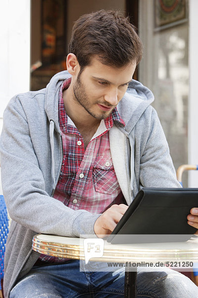 Mann  der auf einem Straßencafé mit einem digitalen Tablett sitzt  Paris  Ile-de-France  Frankreich