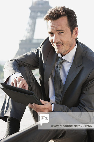 Businessman using a digital tablet with the Eiffel Tower in the background  Paris  Ile-de-France  France
