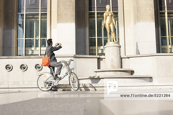 Mann auf dem Fahrrad beim Fotografieren einer Frauenstatue  Palais de Chaillot  Paris  Ile-de-France  Frankreich