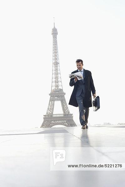 Geschäftsmann beim Spaziergang mit Aktentasche beim Lesen der Zeitung mit dem Eiffelturm im Hintergrund  Paris  Ile-de-France  Frankreich