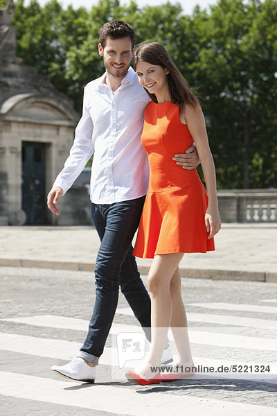 Couple walking with arms around and smiling  Paris  Ile-de-France  France