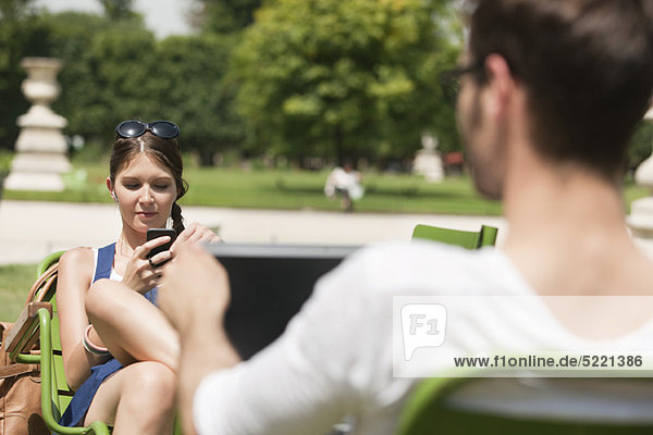 Frau SMS mit Handy  Jardin des Tuileries  Paris  Ile-de-France  Frankreich
