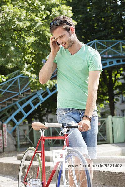 Mann  der mit dem Fahrrad geht und mit dem Handy spricht  Paris  Ile-de-France  Frankreich