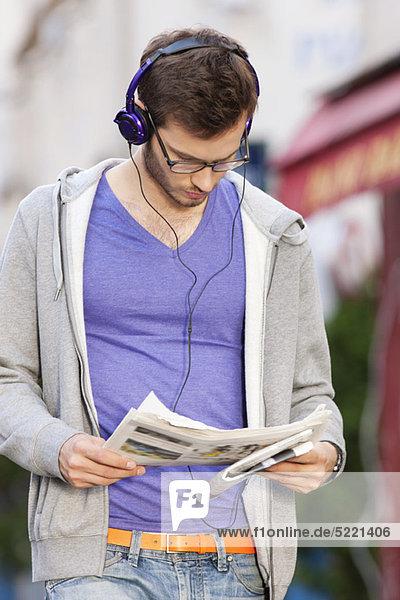 Mann  der eine Zeitung liest  während er Musik hört  Paris  Ile-de-France  Frankreich