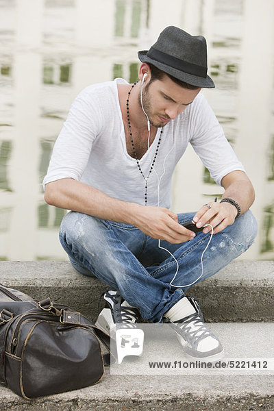 Mann sitzt auf dem Felsvorsprung eines Kanals und hört Musik mit einem MP3-Player  Paris  Ile-de-France  Frankreich
