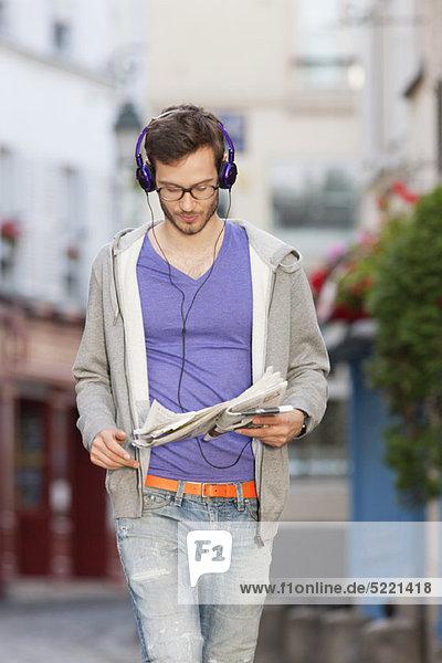 Mann beim Lesen einer Zeitung auf der Straße  Paris  Ile-de-France  Frankreich