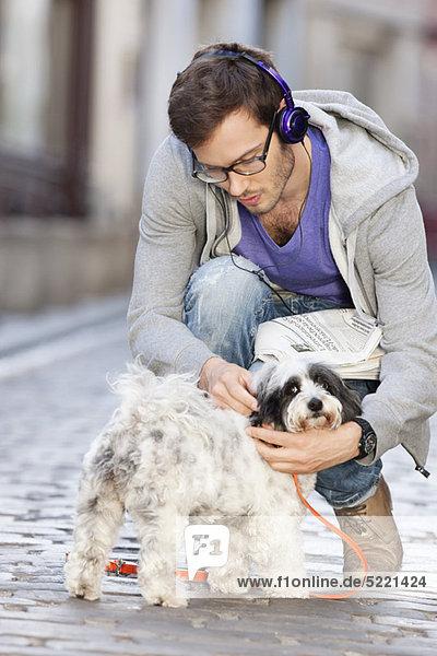 Mann öffnet die Leine eines Hundes  Paris  Ile-de-France  Frankreich