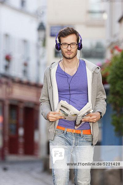 Mann auf der Straße mit einer Zeitung  Paris  Ile-de-France  Frankreich