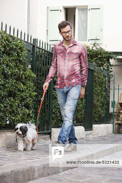 Mann  der einen Hund an der Leine hält  der auf einem Bürgersteig läuft  Paris  Ile-de-France  Frankreich