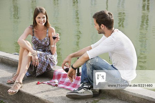 Paar trinkt Rotwein am Rande eines Kanals  Paris  Ile-de-France  Frankreich