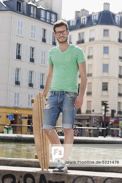 Mann auf der Kante eines Kanals mit Skateboard  Canal St Martin  Paris  Ile-de-France  Frankreich