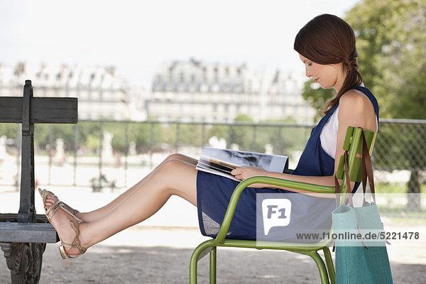 Frau sitzt auf einem Stuhl und liest eine Zeitschrift  Jardin des Tuileries  Paris  Ile-de-France  Frankreich