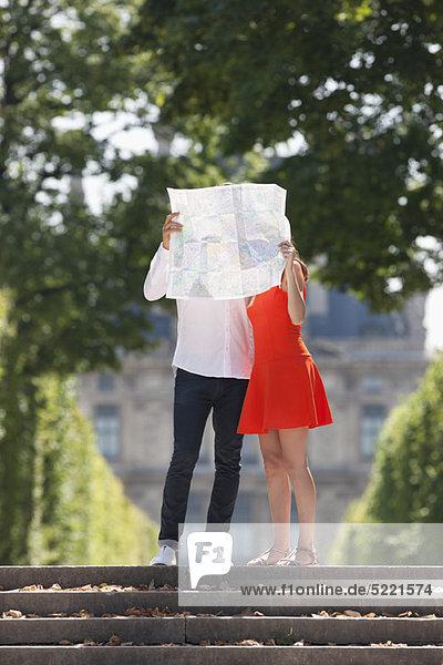 Paar  das eine Karte vor sich hält  Terrasse De l'Orangerie  Jardin des Tuileries  Paris  Ile-de-France  Frankreich