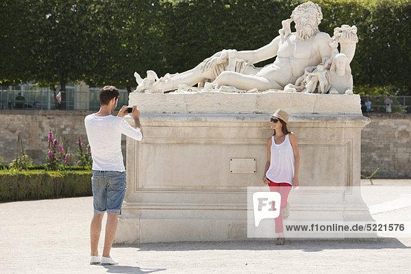 Mann beim Fotografieren einer Frau in der Nähe einer Skulptur in einem Garten  Jardin des Tuileries  Paris  Ile-de-France  Frankreich