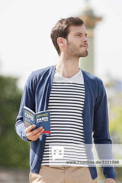 Mann mit Reiseführer  Paris  Ile-de-France  Frankreich