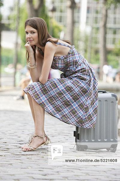 Woman sitting on the suitcase at the roadside  Paris  Ile-de-France  France