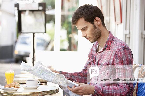 Mann  der an einem Straßencafé sitzt und eine Karte liest  Paris  Ile-de-France  Frankreich
