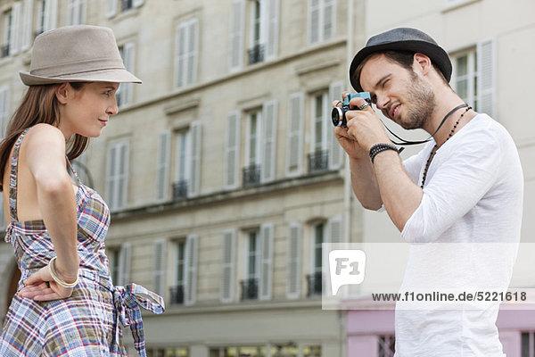 Mann beim Fotografieren einer Frau mit der Hand auf der Hüfte  Paris  Ile-de-France  Frankreich
