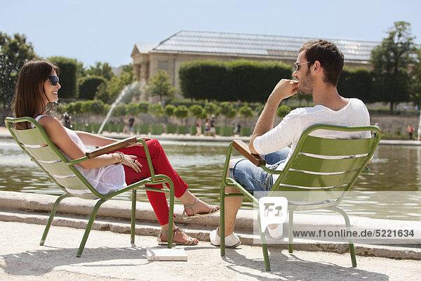 Paar auf Stühlen in der Nähe eines Teiches in einem Garten  Bassin achteckig  Jardin des Tuileries  Paris  Ile-de-France  Frankreich