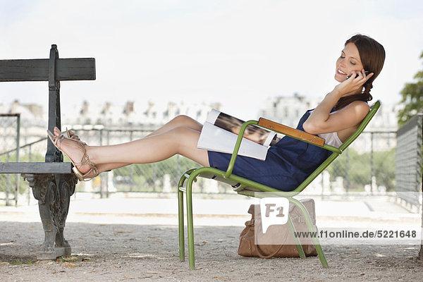 Frau auf einem Stuhl liegend und auf einem Handy sprechend  Jardin des Tuileries  Paris  Ile-de-France  Frankreich