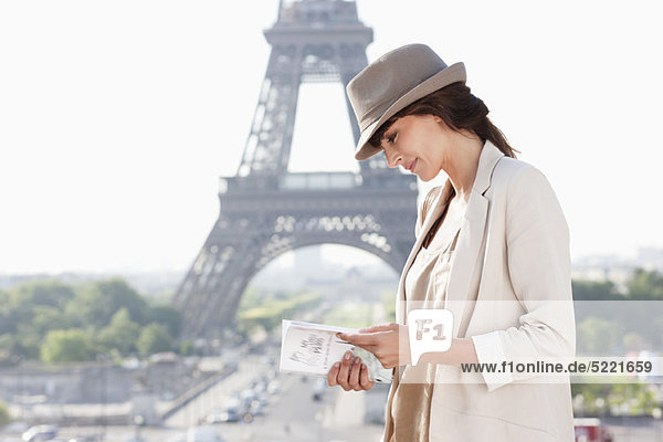 Woman reading a guide book with the Eiffel Tower in the background, Paris, Ile-de-France, France KY378021
