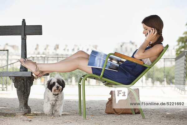 Woman sitting in a chair reading a magazine and talking on a mobile phone  Jardin des Tuileries  Paris  Ile-de-France  France