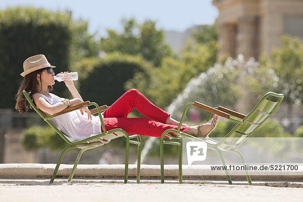Frau sitzt auf einem Stuhl und trinkt Wasser  Bassin achteckig  Jardin des Tuileries  Paris  Ile-de-France  Frankreich