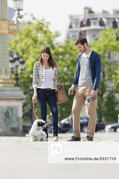 Frau hält einen Welpen an der Leine mit einem Mann neben ihr  Paris  Ile-de-France  Frankreich