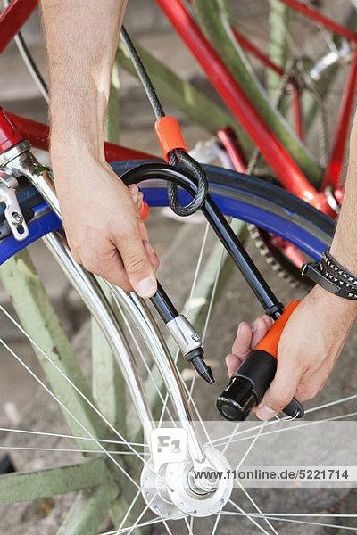 Nahaufnahme der Hände eines Mannes  der sein Fahrrad verschließt  Paris  Ile-de-France  Frankreich