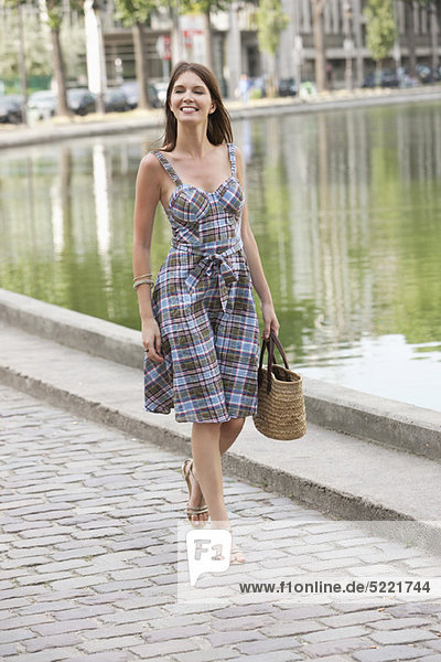 Woman walking near a canal and smiling  Paris  Ile-de-France  France