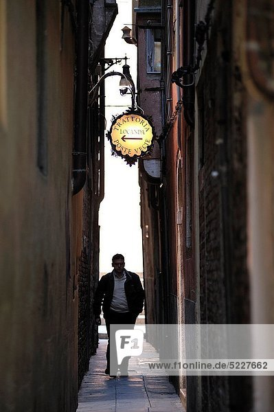 Person walking backlight by a narrow alley in the city of Venice  Italy  Europe