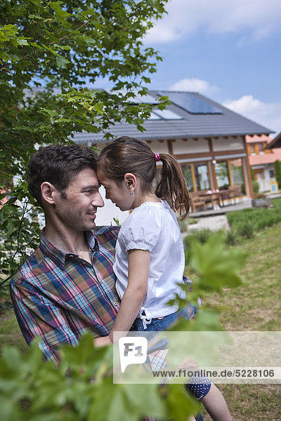 Father with daughter in front of Lehner energy house  Poing  Bavaria  Germany  Europe