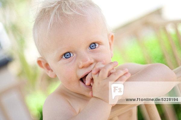 Kleiner blonder Junge mit der Hand im Mund  Portrait