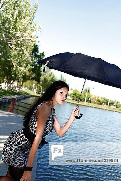nahe  Außenaufnahme  Frau  Regenschirm  Schirm  alt  freie Natur  Teich  Jahr